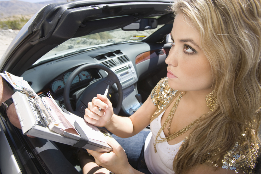 Young woman writing on traffic ticket